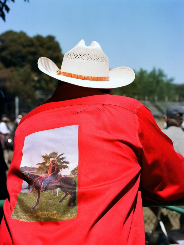 Cowboy Greg Bradley Sr. at The Bill Pickett Invitational Rodeo in Oakland, California. July 2017. He's wearing a shirt with a photo of him on it.